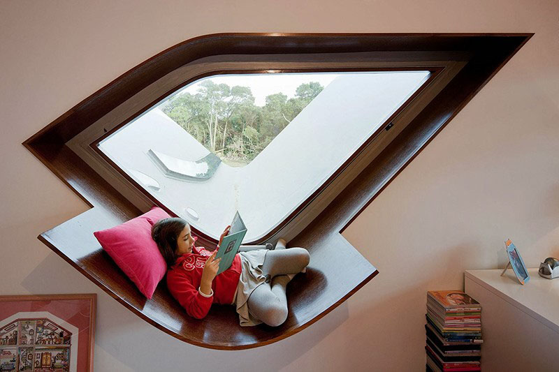 This geometrically shaped window has a built-in wood frame with an additional support that acts as a curved window seat.