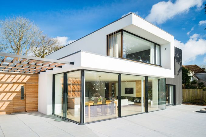 This modern house has large glass windows / doors that open up to the backyard.