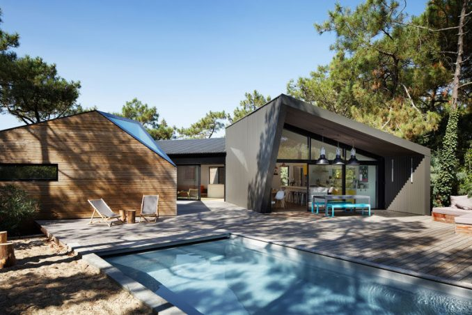 Atelier du Pont have designed a new a holiday house with swimming pool in Cap Ferret, France, that sits among a small forest of strawberry trees, yucca and pines.