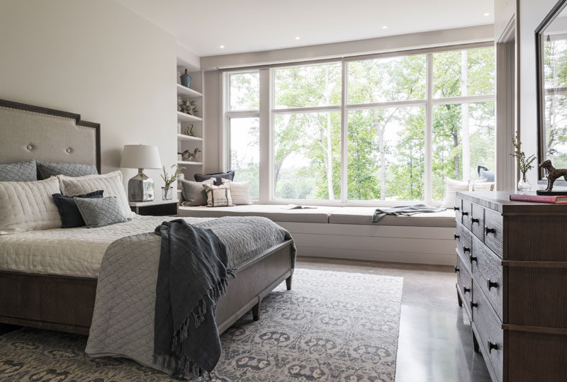 In another bedroom, there's a built-in window seat that runs the length of the windows, and at one end, there's a built-in bookshelf. #Bedroom #WindowSeat #Shelving