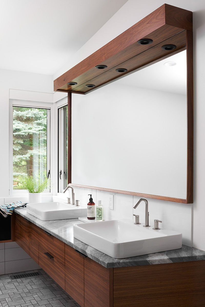 In this modern master bathroom, a dark wood-framed mirror sits above the vanity with dual sinks and a stone counter. #MasterBathroom #BathroomDesign