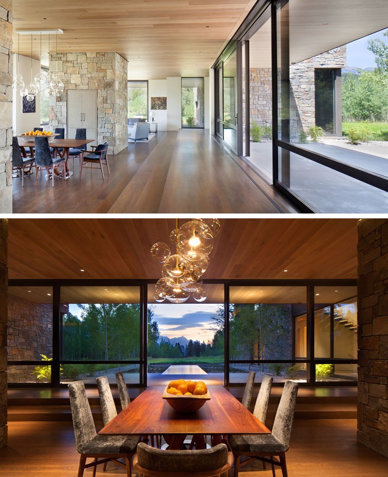 Inside this modern house, white oak wood floors are used throughout, while in the dining area, the wood dining table lines up with the water feature outside. #OakFlooring #DiningRoom