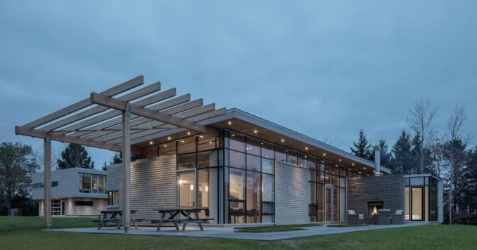 This modern house in Nova Scotia has an extended roof that creates a pergola for an outdoor entertaining space. #ModernHouse #ModernPergola