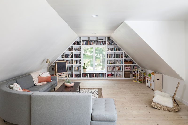This modern living room /play area has a custom designed bookshelf that wraps around the window. #Bookshelf #Window #LivingRoom