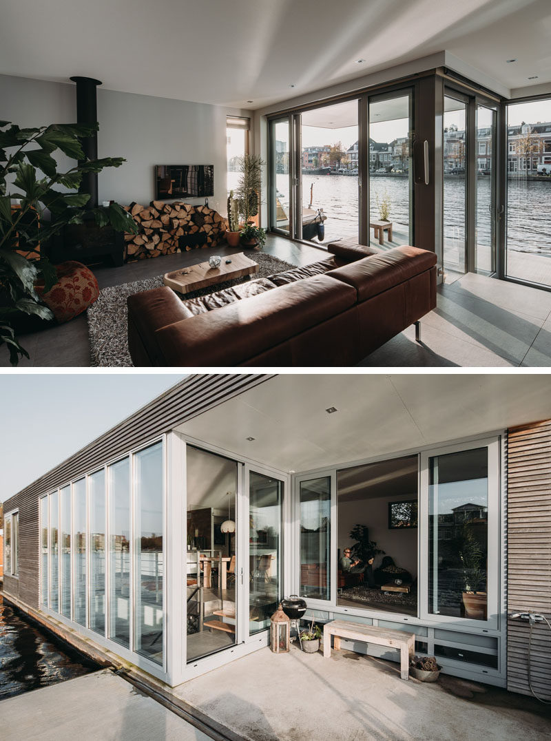 In the living room of this modern houseboat, there's a wood-burning fireplace for colder months, and in the warmer months, a sliding door can be opened to provide access to a small deck. #Fireplace #Windows #LivingRoom