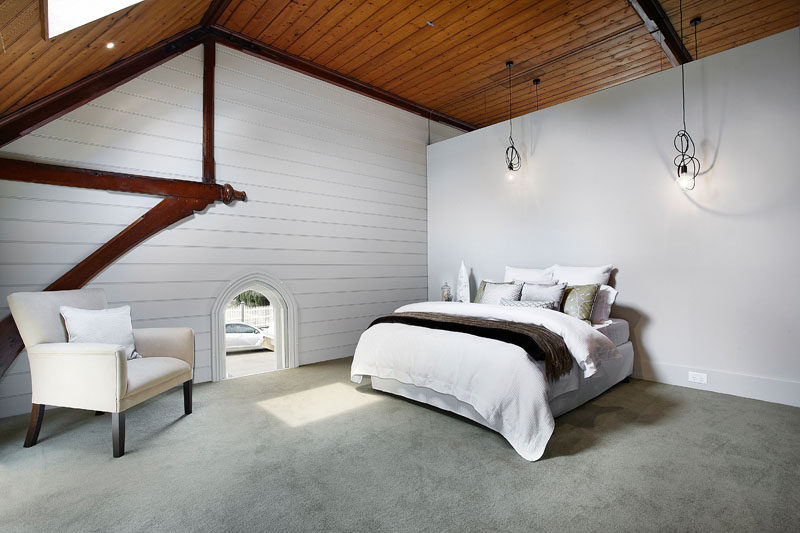 This minimalist bedroom shows of the shape of the original church and its wood ceilings and architectural details. #BedroomDesign #ChurchConversion