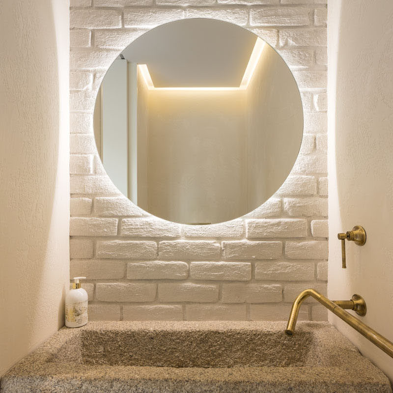 This small powder room has has areclaimed granite trough as the sink and a backlit mirror. #PowderRoom #BacklitMirror #GraniteSink