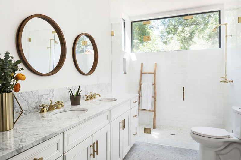 In this contemporary bathroom, round mirrors hang above the double-sink vanity that's topped with Carrara marble, while a glass shower surround allows the natural light from the window to flow through the space. #BathroomDesign #WhiteBathroom