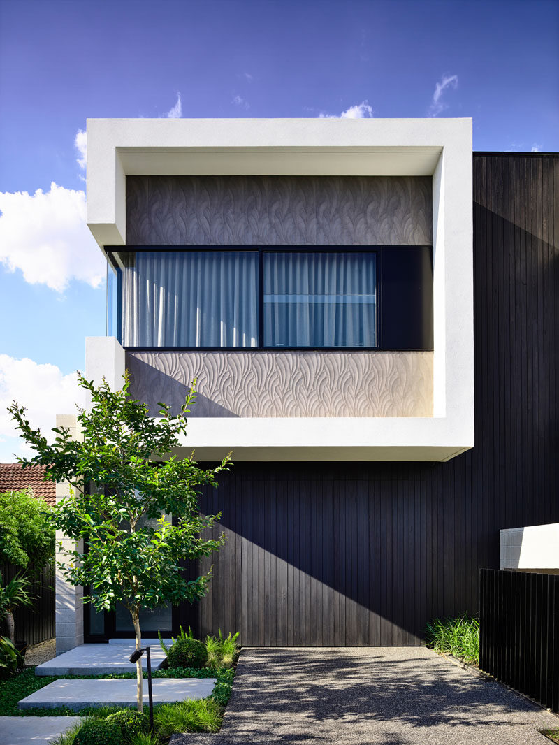 This modern duplex conceals the garages and utility room behind black stained vertical timber cladding #Architecture #HouseDesign #Duplex