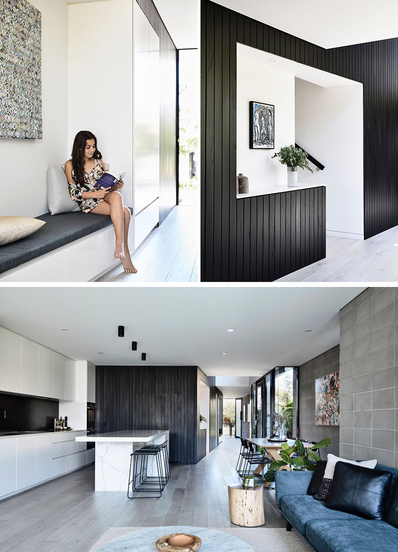 This modern house has the entryway defined by black stained time cladding, that wraps around a built-in bench and the stairs, and then travels through to the kitchen.