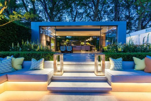 This garden features a sunken patio area with built-in seating, and a pavilion that houses a dining area and kitchen. #Landscaping #LandscapeDesign #Garden #Backyard