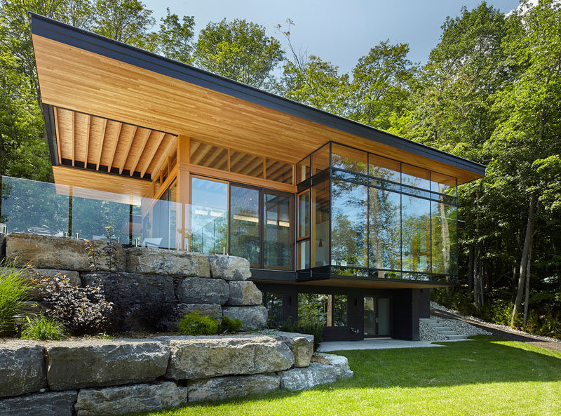 A new modern cottage with a cantilevered roof, and a landscaped section with lounge areas, were added to an existing smaller cottage. #ModernArchitecture #Landscaping #ModernCottage #CantileveredRoof