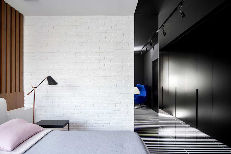 Widawscy Studio Architektury have designed a modern master bedroom that features a white brick wall, a wood slat accent wall, black and white striped flooring, black closets, and pop of bright blue in the form of an chair. #MasterBedroom #StripedFlooring #BlackClosets