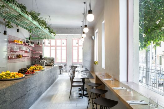 Amit Design Studio has recently completed Bana, an organic food cafe that's located in Tel Aviv, Israel, and has design features like pink metal grid shelving and a large basket filled with plants that hangs from the ceiling. #CafeDesign #ModernCafe #InteriorDesign