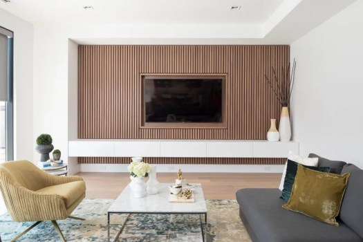 This modern living room features a wood slat accent wall that surrounds the TV and provides a row of white storage cabinets. #TVWall #InteriorDesign #AccentWall #LivingRoom