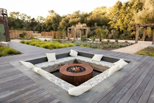 Central to this landscaped backyard is a wooden pathway that leads to a large sunken lounge with bench seating and a fire pit. #SunkenLounge #Landscaping #Firepit
