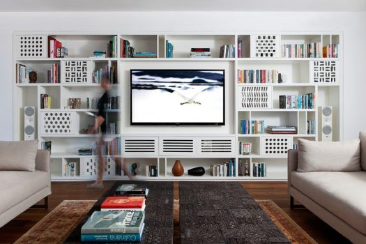 This modern apartment has a custom-designed shelving unit in the living room, that's filled with playful patterns and plenty of storage. #Shelving #LivingRoom #Library #Bookshelf