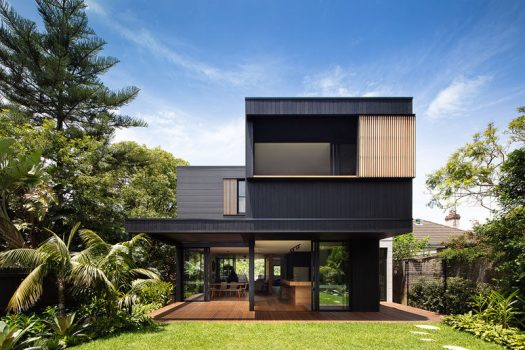 The exterior of this modern house is clad in Blackened Cambia Ash and Scyon Stria, while sliding glass doors open the home up to the backyard. #ModernHouse #ModernArchitecture