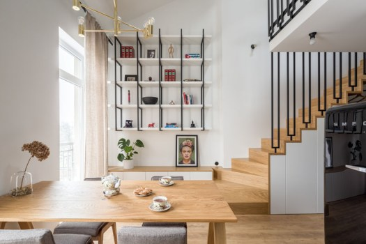 This modern apartment with a mezzanine features a simple hanging bookcase that was designed to display the homeowners collection of souvenirs picked up on their travels. #Shelving #InteriorDesign #ApartmentInterior