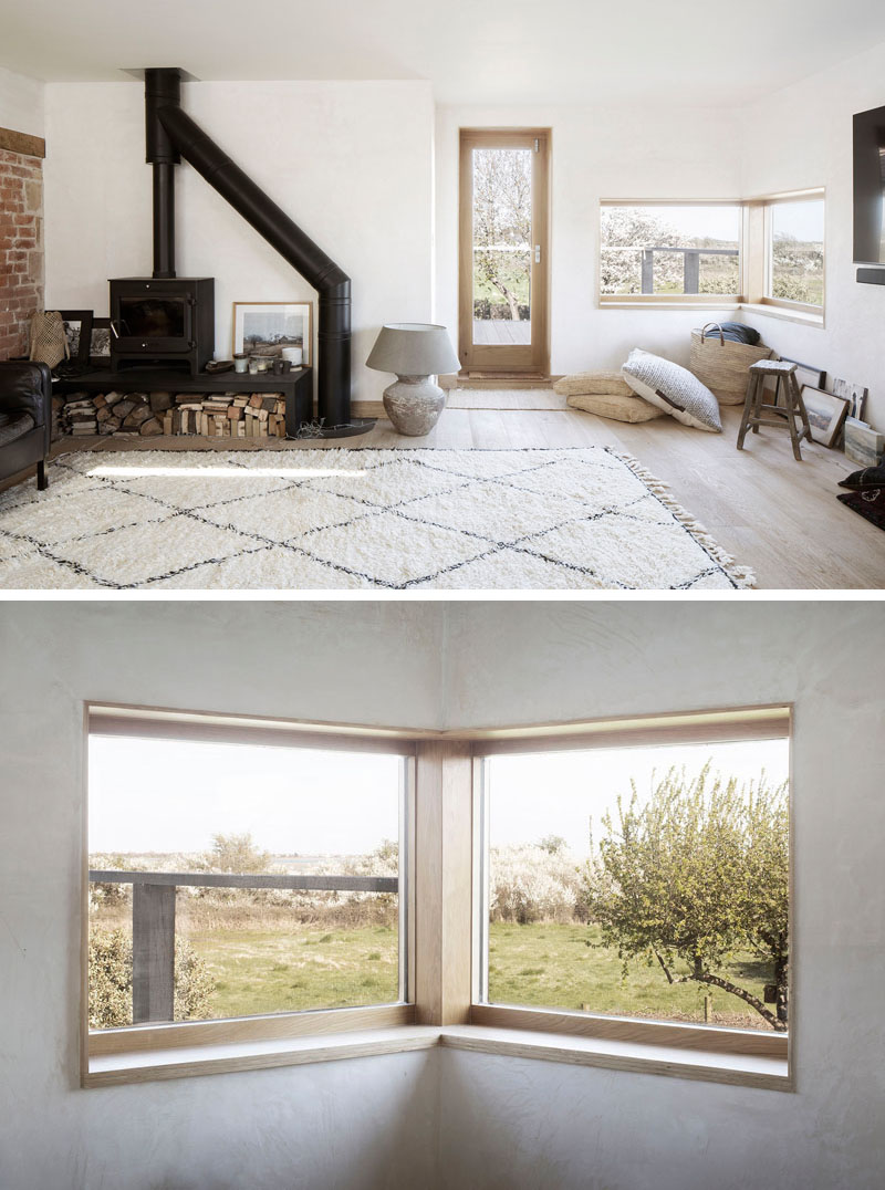 The main living space of this house addition features a wood-framed corner window, referencing an open book set into the wall at the height of a desk. #CornerWindow #LivingRoom