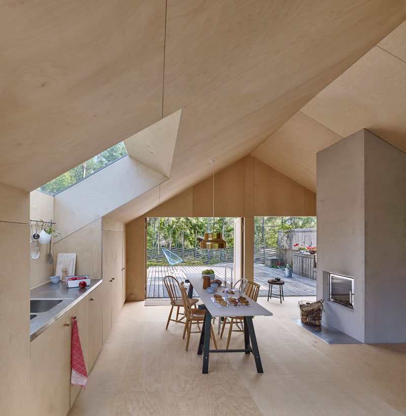 Windows filter the light through to the bright interior of this modern house that features birch plywood walls, ceiling, and floor. #PlywoodWalls #PlywoodInterior #Windows #Kitchen #Fireplace