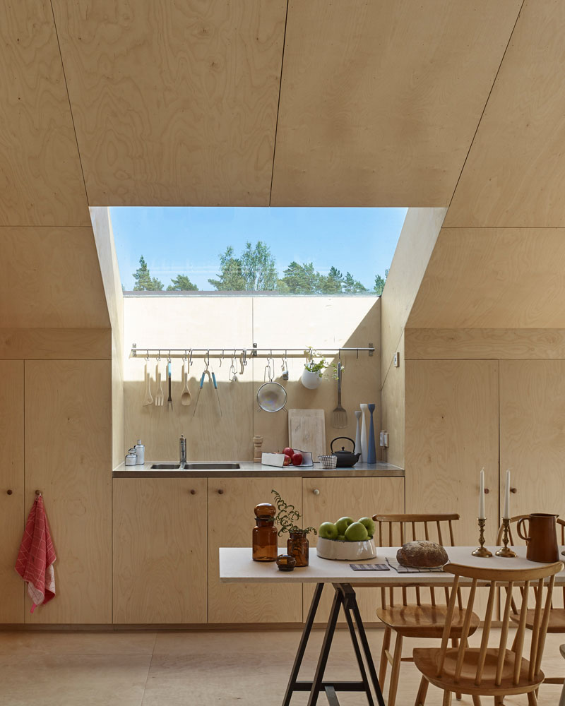 Windows filter the light through to the bright interior of this modern house that features birch plywood walls, ceiling, and floor. #PlywoodWalls #PlywoodInterior #Windows #Kitchen