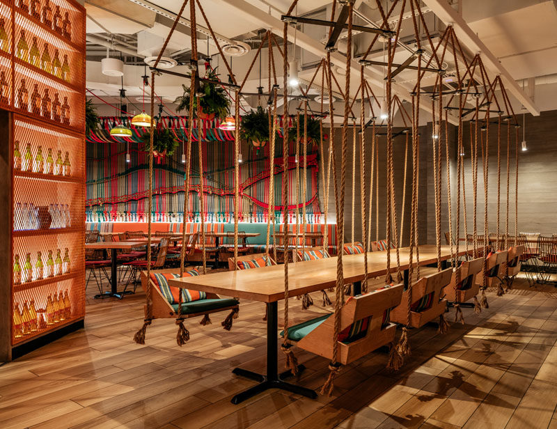 Restaurant Ideas - In this modern restaurant, a large wood communal table is surrounded by swinging chairs, adding to the playful, relaxed vibe of the space. #RestaurantIdeas #RestaurantSeating #HangingChairs