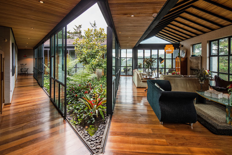 Garden Ideas - Nestled within the mountains, the layout of this modern black house provides a space for an open interior garden. #Garden #InteriorGarden #HouseDesign