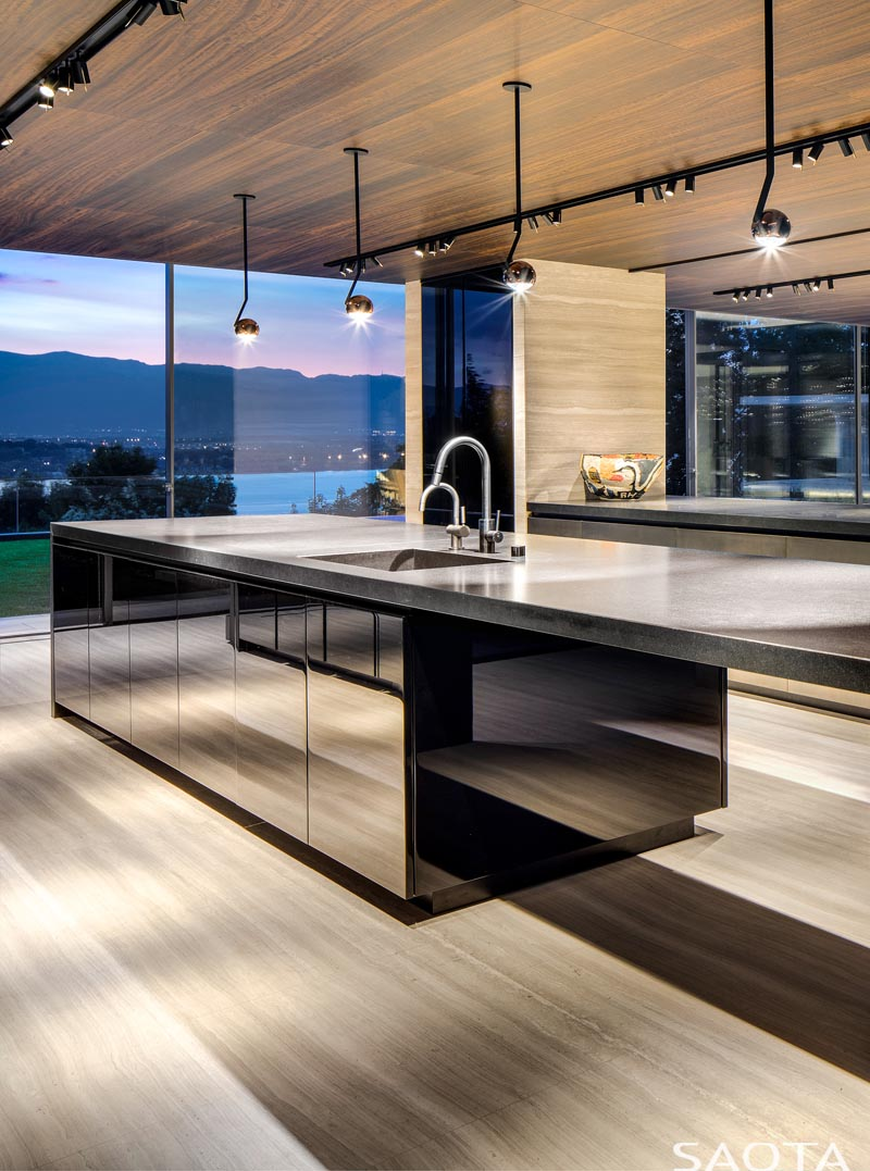 The wood ceiling in this modern kitchen adds warmth, while the kitchen island cabinetry has a mirrored finish. #KitchenDesign #MirroredCabinets
