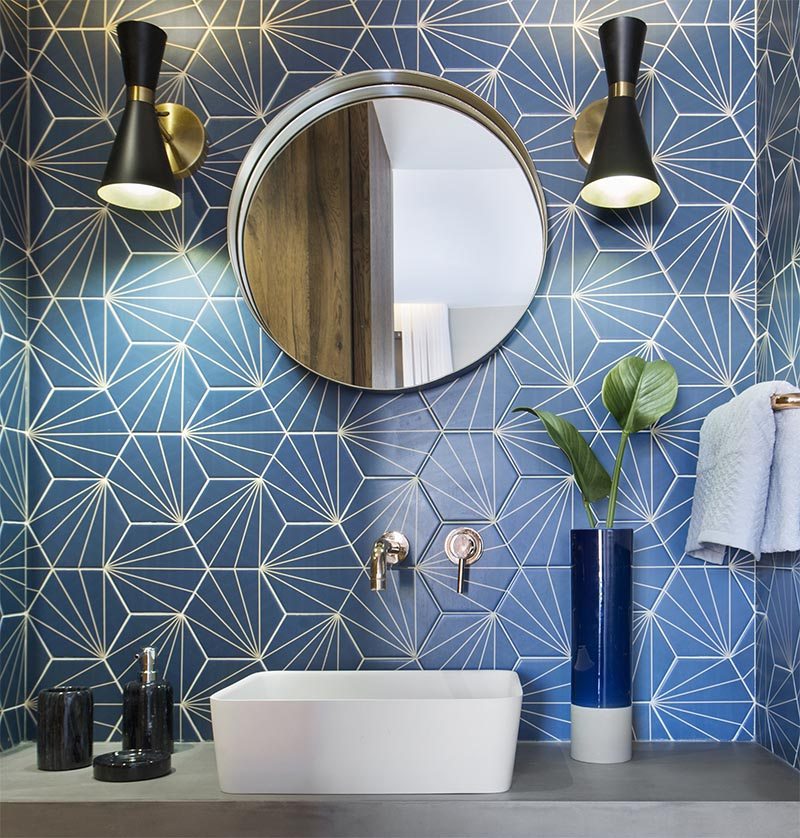 This modern blue bathroom has eye-catching starburst patterned tiles, rose gold tap and faucet, a concrete countertop, black and gold lighting, and a round mirror. #BlueBathroom #StarburstTile #ModernBathroom #BathroomIdeas