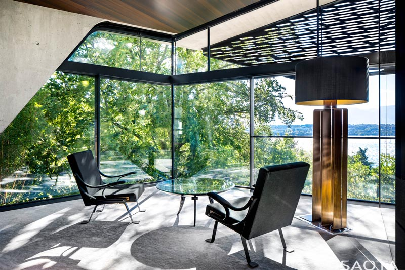 This modern home office takes advantage of the spectacular views, and enjoys the shade from the trees and the perforated screen on the exterior of the house. #ModernHomeOffice #GlassWalls