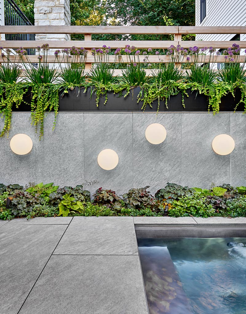 This modern outdoor space features a stone-look porcelain tile, while native, drought-resistant plantings add a natural touch, and globe light fixtures add an artistic flair to the wall by the custom-designed spa. #Landscaping #BlackSteelPlanters #OutdoorLighting #OutdoorEntertaining