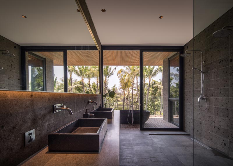 In this modern bathroom, the freestanding bathtub is located on the covered balcony, while inside, hidden lighting behind the mirror highlights the stone wall and vanity. #ModernBathroom #BathroomDesign #OutdoorBathtub