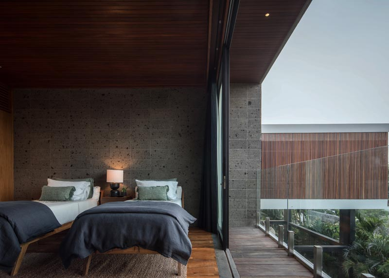 In this modern bedroom, the stone walls provide a earthy grey backdrop for the beds, while a sliding glass door opens to a small balcony with a glass railing, that provides uninterrupted views of the treetops and the outdoor space below. #ModernBedroom #Sandstone #BedroomDesign #Balcony