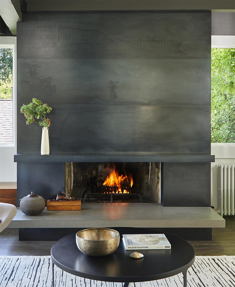 This modern blackened steel fireplace surround with a concrete hearth, creates an eye-catching detail in the living room.  #ModernFireplace #SteelFireplaceSurround #SteelFireplace #ConcreteHearth #ModernLivingRoom