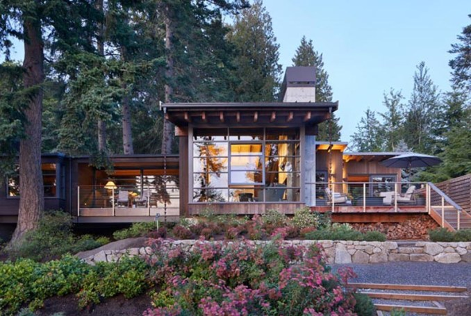 This modern house has deep overhanging eaves with exposed cedar beams, offering protection from the weather and connecting to rain chains, aiding with the flow of rainwater into the garden. #OverhangingEaves #DeepEaves #ModernArchitecture #ExposedBeams #CedarBeams #HouseDesign #PacificNorthwest