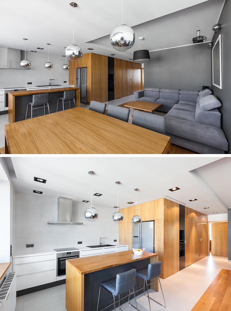 Architecture and interior design firm mode:lina has completed an apartment in Poznan, Poland, and instead of mounting a television in the living room, they included a drop-down projector screen. #DropDownProjectorScreen #ProjectorScreen #InteriorDesign #LivingRoom #WoodKitchen #GreyLivingRoom