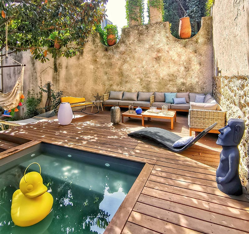 A backyard design that includes a raised lounge, a small pool, and hammocks.