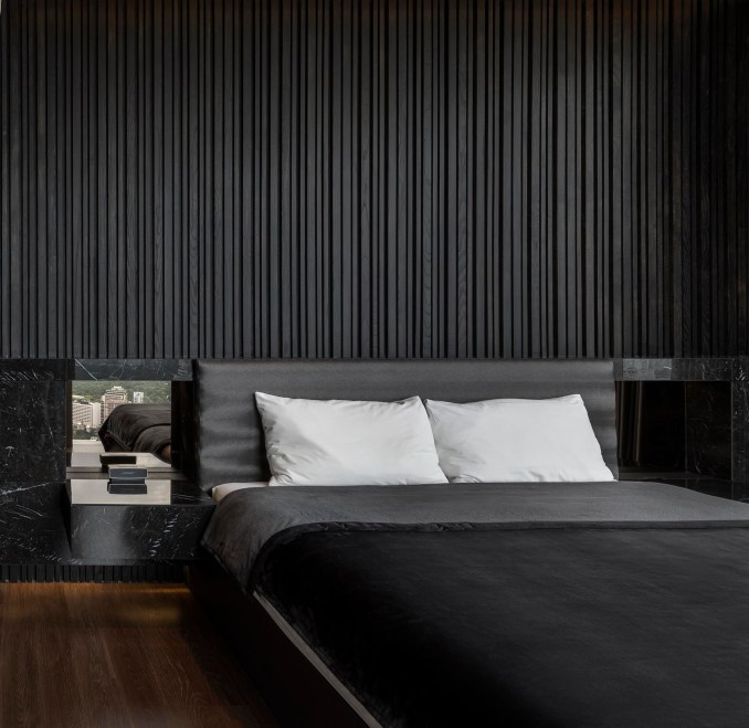 A modern black bedroom with a textured wood accent wall.