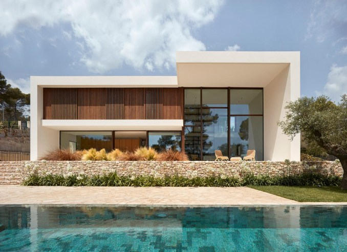 A modern house design with an off-white exterior, wood and steel accents, and a swimming pool.