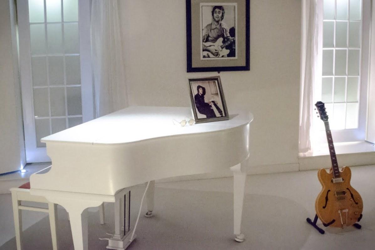 Beatles Story: Glasses, guitar, portraits of John Lennon