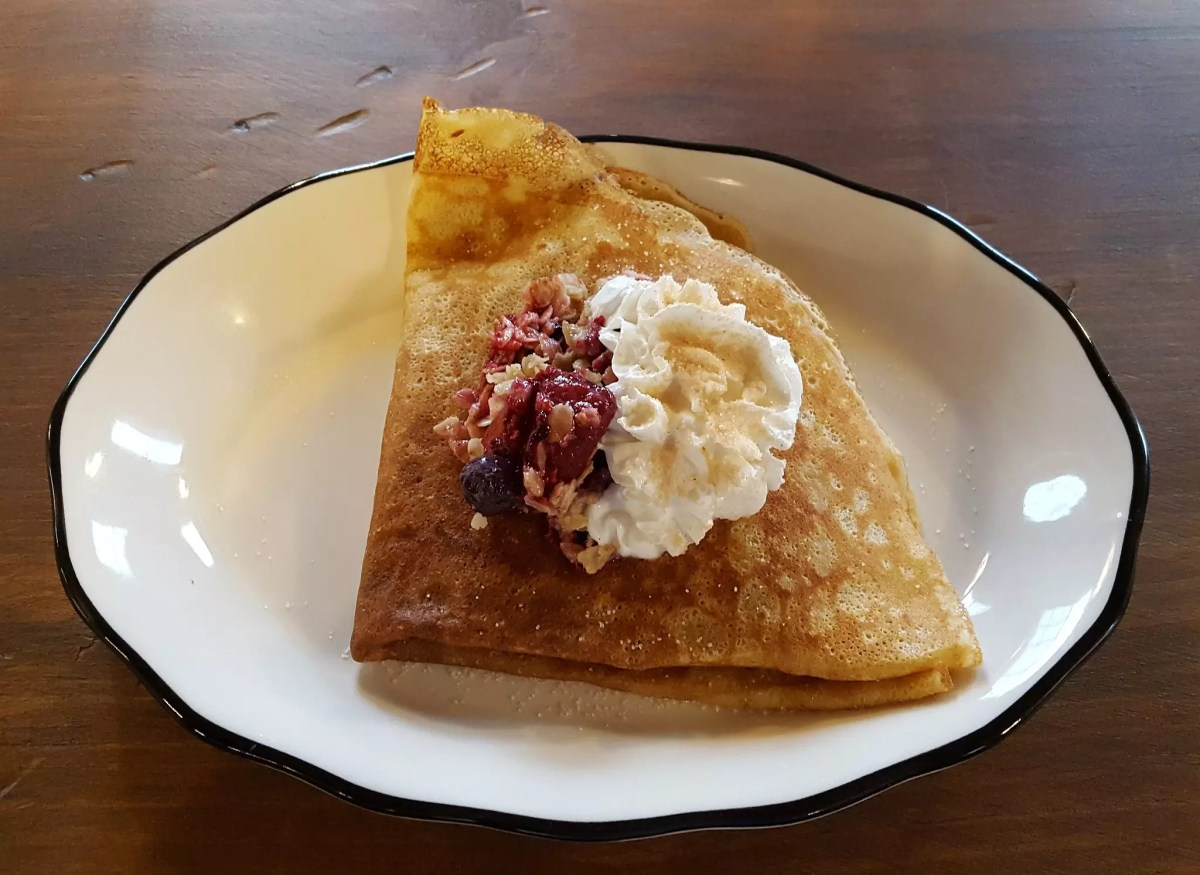 Thin pancake with fillings topped with whipped cream ad fruits