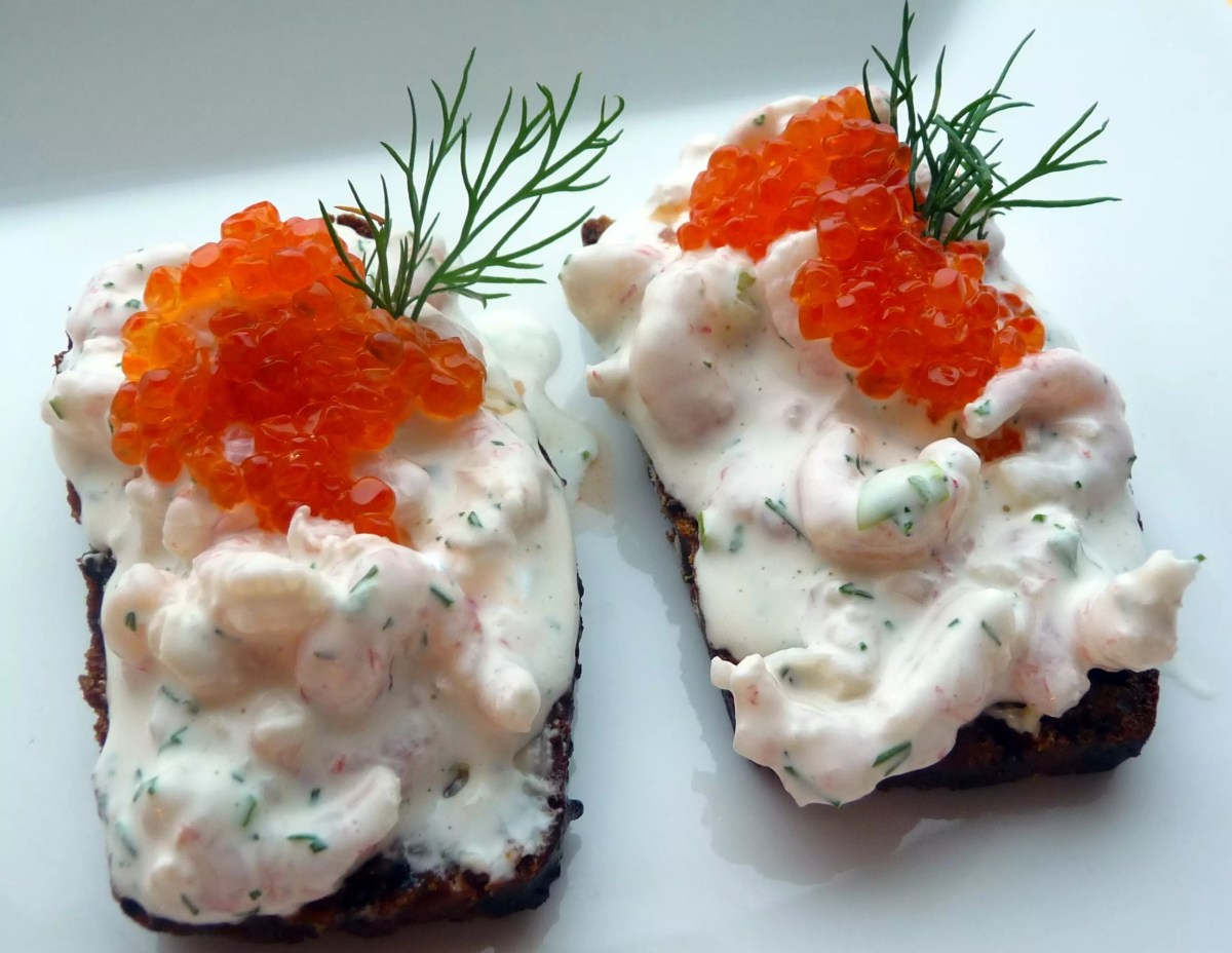 A piece of toasted bread with a prawn salad topped with salmon roe - photo by Prawns Skagen under CC BY 2.0