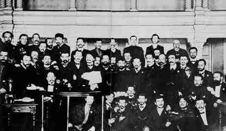 Ο Τρότσκι (με τον φάκελο στα χέρια) μεταξύ των μελών του σοβιέτ της Αγίας Πετρούπολης, το 1905, κατά την διάρκεια της δίκης τους