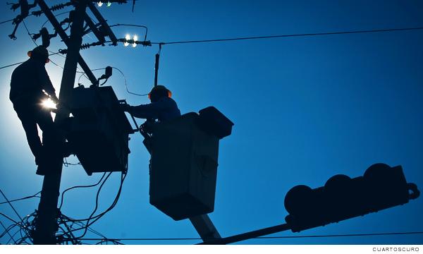 Trabajadores cerca de generadores de energía sobre un poste