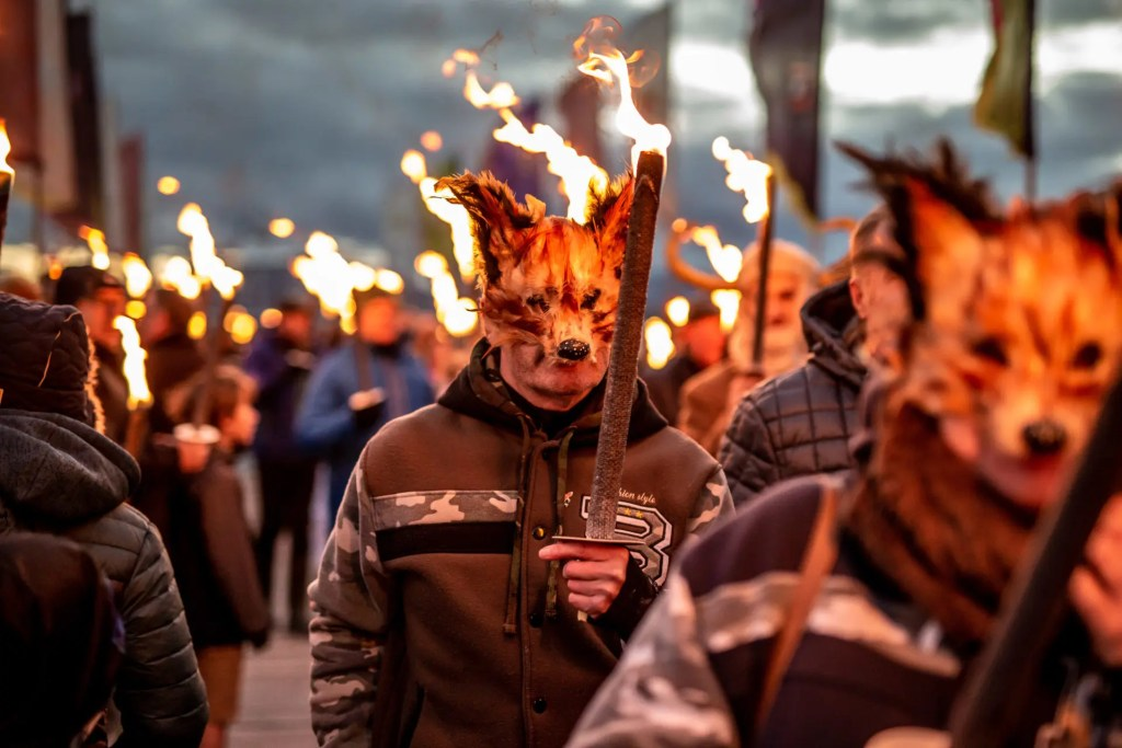 Winter Droving Ullswater Masked members of the public walk with fire torches