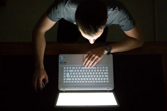 Man looking at computer screen in the dark