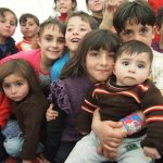 Children of Refugees smile for the camera.