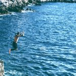 man jumping off a cliff into the ocean