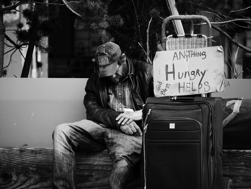 """homeless man with his head down, sign that says """"hungry, anything helps"""""""